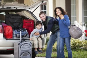 Family with little boy going on vacation, loading luggage into car.
